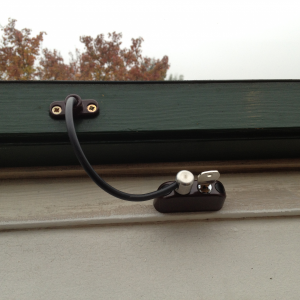 Brown Cable Restrictor fitted to high level Velux window opener.