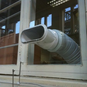 Air conditioning hose fitted through glass